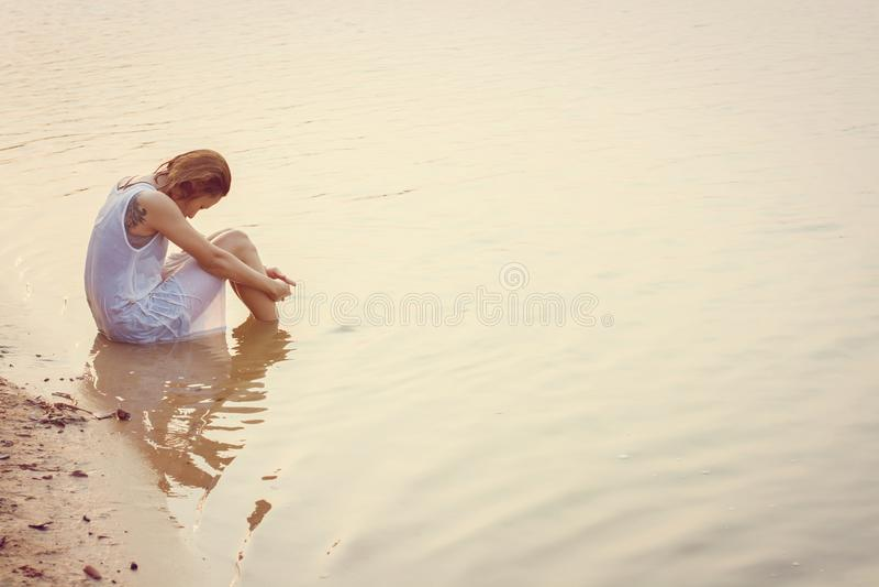 Droevige vrouwenzitting op de strandzonsondergang teleurgesteld, droefheid stock foto