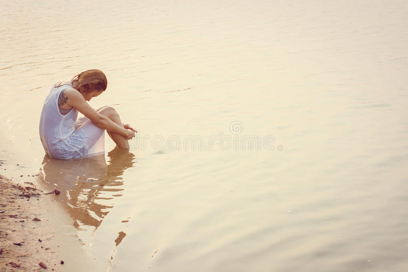 Droevige vrouwenzitting op de strandzonsondergang teleurgesteld, droefheid stock afbeelding