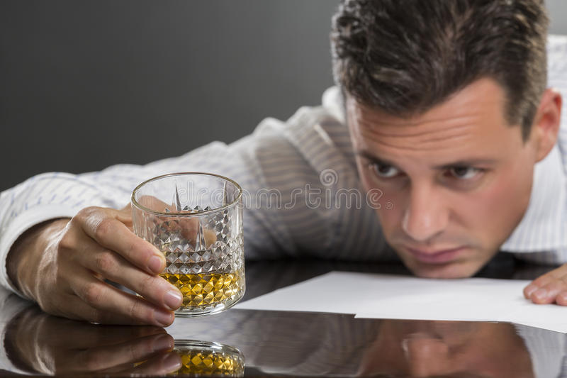Droevige zakenman het drinken alcohol stock afbeelding