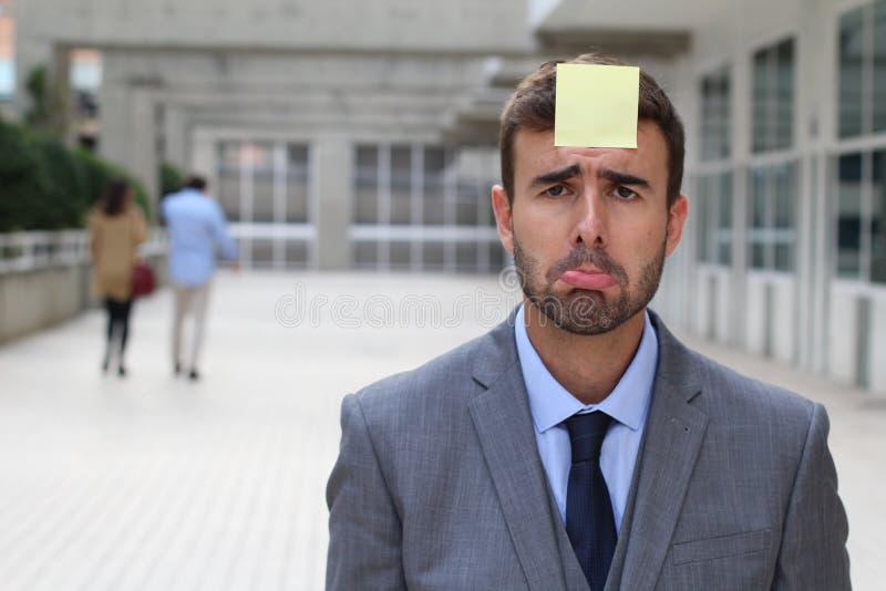 Droevige zakenman met een nota over zijn voorhoofd royalty-vrije stock foto