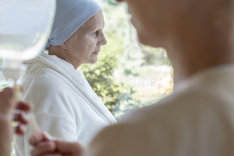 Droevige zieke hogere vrouw met kanker tijdens chemotherapie in het ziekenhuis royalty-vrije stock foto