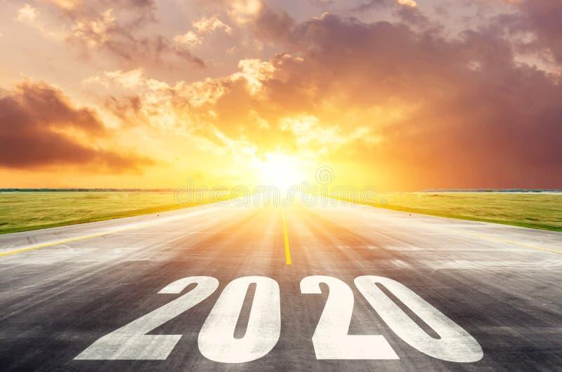 Droga asfaltowa drogowa z napisem 2020 rok z wschodzącym słońcem rano Koncepcja początku nowych celów i fotografia stock