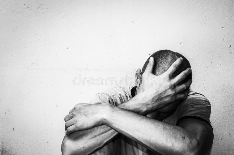 A droga e o álcool desabrigados do homem dedicam-se assento sozinho e deprimido na rua que sente concentrados documentável ansios imagem de stock