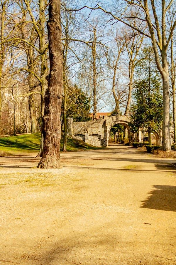 Droga gruntowa między drzewami w Proosdij parku z starym kamienia mostem w tle zdjęcie royalty free