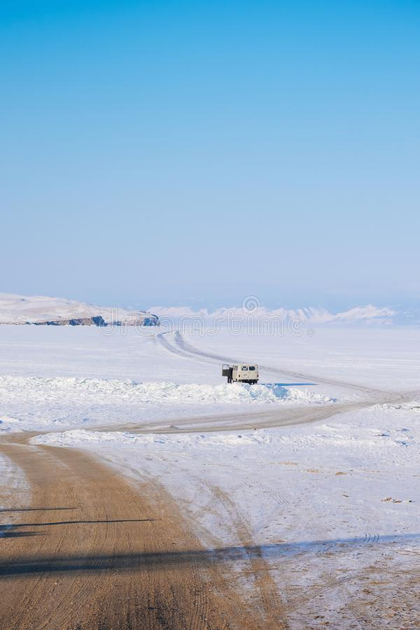 Droga gruntowa zamarznięty jezioro Śnieżna Marznąca droga na jeziorze Góra jest naprzeciw lodowatej drogi zdjęcie stock
