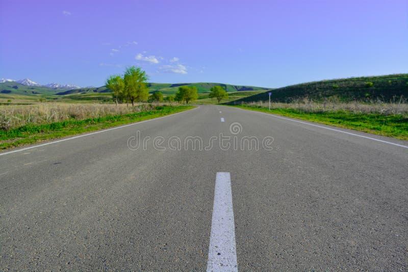 Droga krawędź zielone wzgórza jasny dzień Góry Alatau « zdjęcie stock
