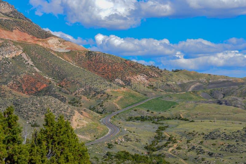 Droga meandruje wzdłuż bazy ogromny pasmo górskie w północnym Wyoming obraz royalty free
