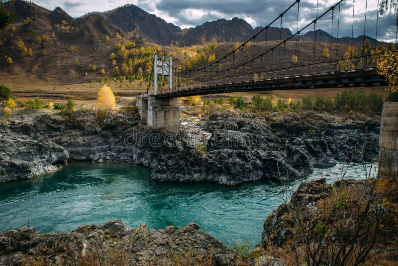 Droga most nad turkusową Katun rzeką w Altai górach Rosyjska jesień w Syberia Nieprawdopodobny krajobraz z metalu mostem zdjęcia royalty free