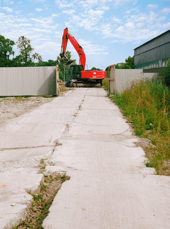 Droga na betonowych płytach brama za którym zaczyna czerwonego ekskawator za ogrodzeniem budowa obrazy royalty free