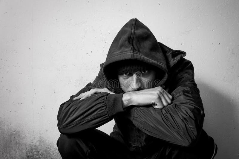 Droga senza tetto dell'uomo e persona dedita dell'alcool che si siede da solo e depressa sulla via in vestiti di inverno che rite fotografia stock