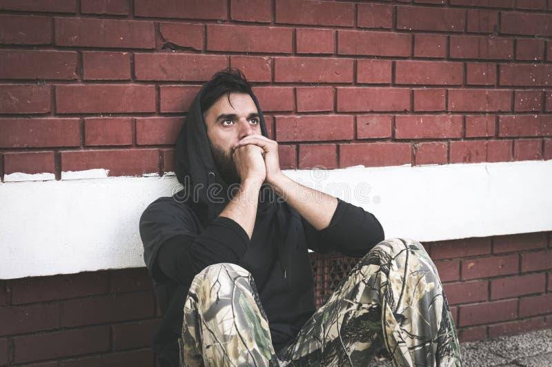 Droga sin hogar del hombre y adicto al alcohol que se sienta solamente y deprimido en la calle fotos de archivo