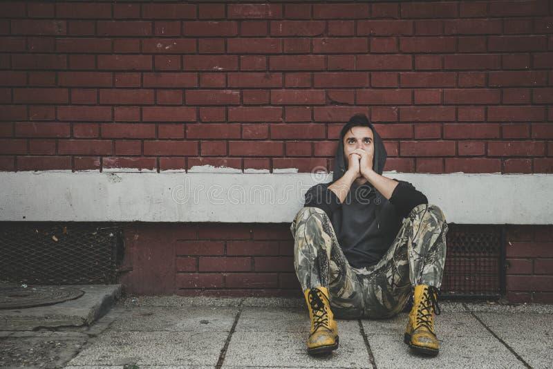 Droga sin hogar del hombre y adicto al alcohol que se sienta solamente y deprimido en la calle fotografía de archivo