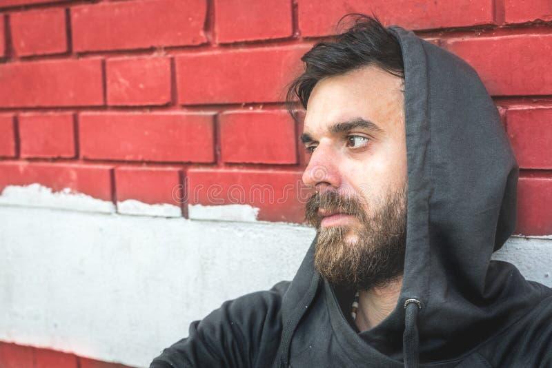 Droga sin hogar del hombre y adicto al alcohol que se sienta solamente y deprimido en la calle foto de archivo