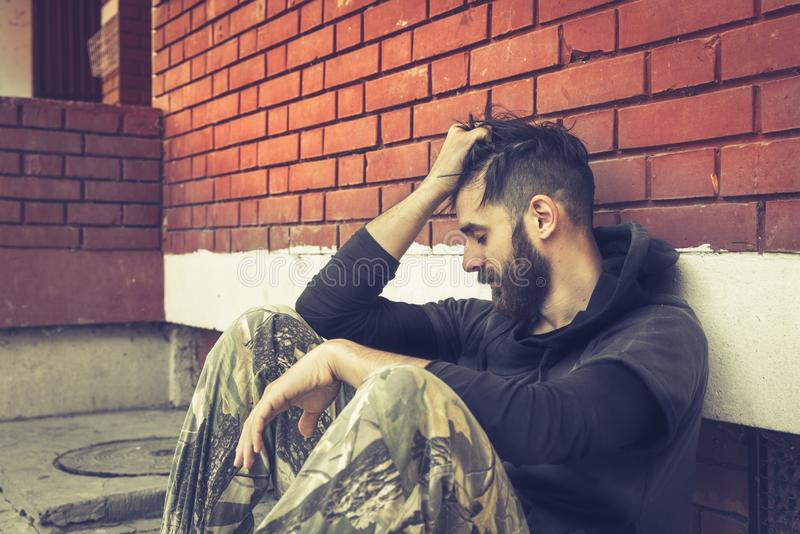 Droga sin hogar del hombre y adicto al alcohol que se sienta solamente y deprimido en la calle imagen de archivo libre de regalías