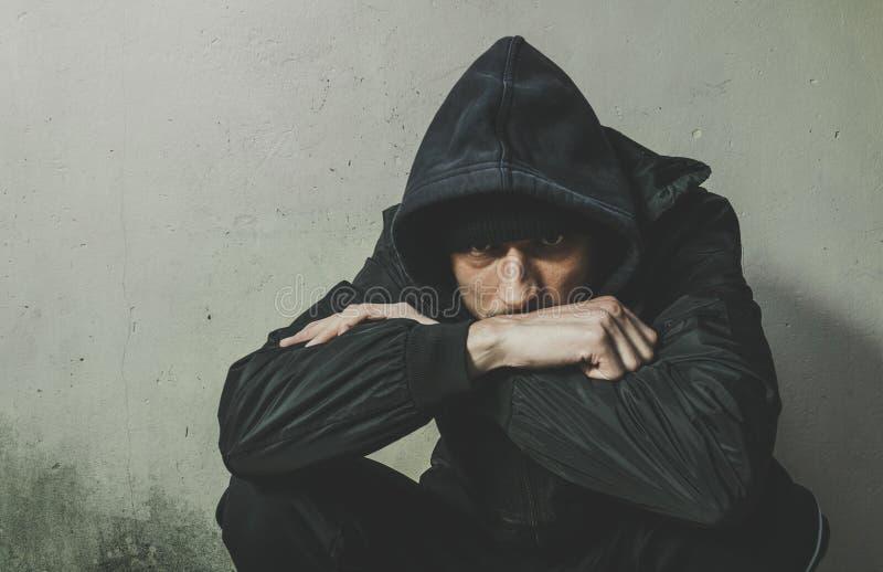 Droga sin hogar del hombre y adicto al alcohol que se sienta solamente y deprimido en la calle en la ropa del invierno que siente imagen de archivo