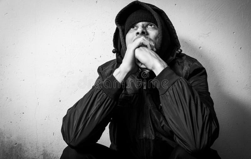Droga sin hogar del hombre y adicto al alcohol que se sienta solamente y deprimido en la calle en la ropa del invierno que siente fotos de archivo