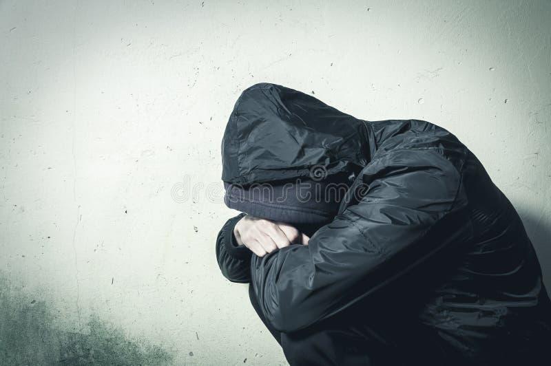 Droga sin hogar del hombre y adicto al alcohol que se sienta solamente y deprimido en la sensación de la calle ansiosa y sola en  imagen de archivo