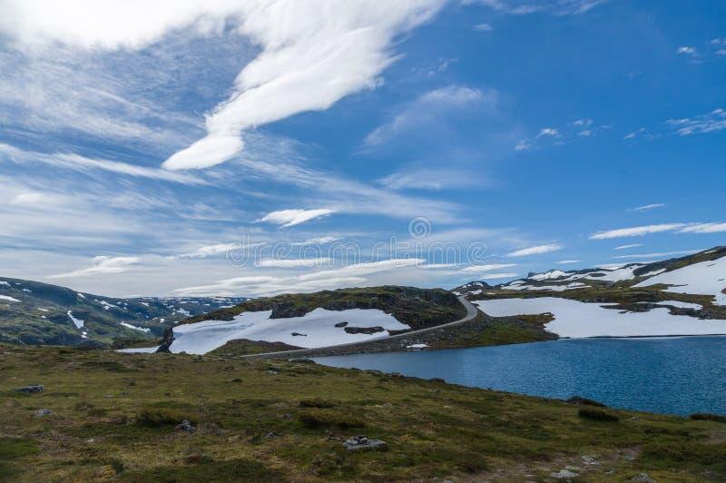 Droga w lata śnieżnym średniogórzu pod niebieskim niebem obrazy stock