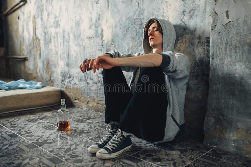Drogadicto con la jeringuilla que se sienta en piso después de dosis imágenes de archivo libres de regalías