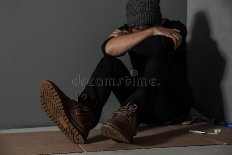 Drogadicto empedrado que se sienta en piso cerca de la pared fotografía de archivo libre de regalías