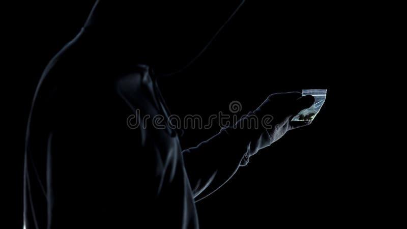 Drogadicto en la sudadera con capucha que sostiene el paquete con las drogas, comprobando la calidad de la marijuana fotografía de archivo