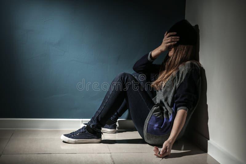 Drogadicto femenino con la jeringuilla que se sienta en piso Concepto de apego foto de archivo