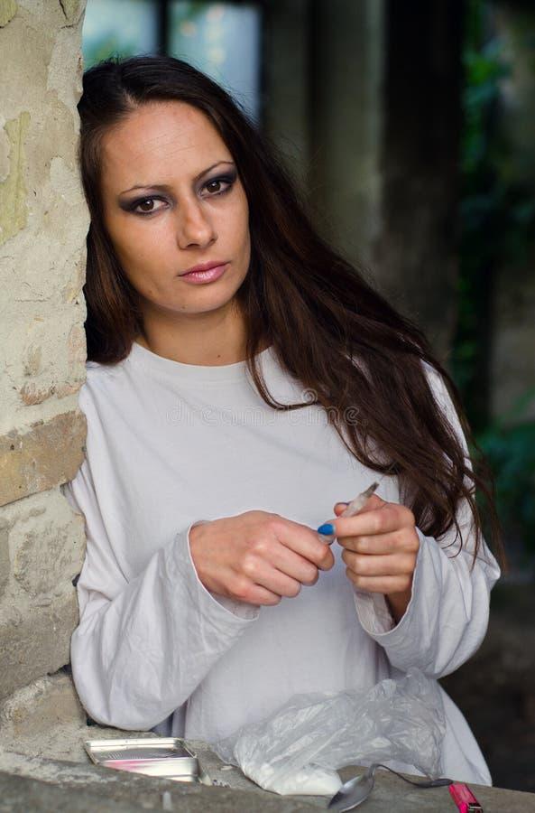 Drogadicto femenino joven que se prepara para tomar la heroína fotos de archivo