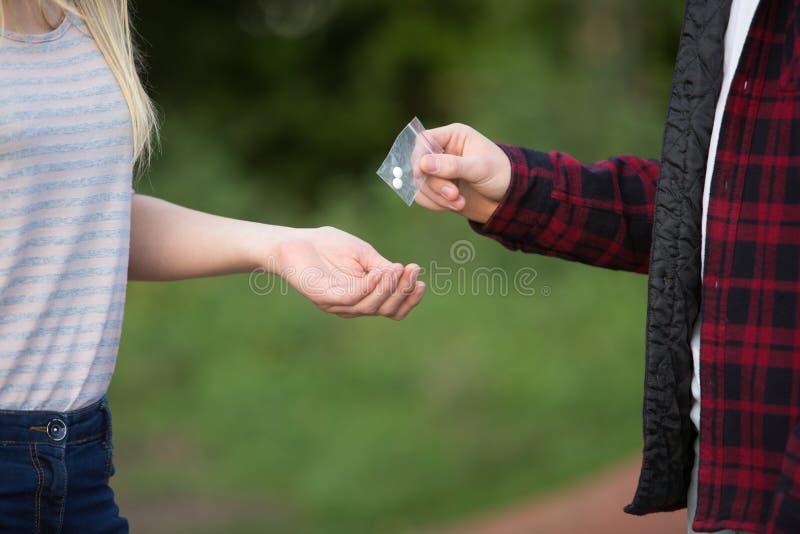 Drogas de compra do adolescente no campo de jogos do negociante foto de stock