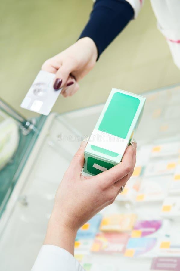 Drogas de la farmacia que compran con la tarjeta plástica foto de archivo