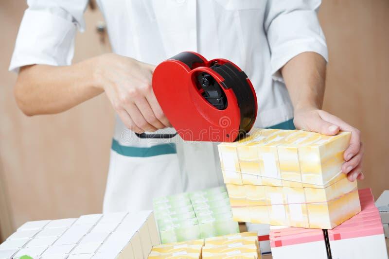 Drogas de rotulagem da mulher do químico da farmácia imagens de stock