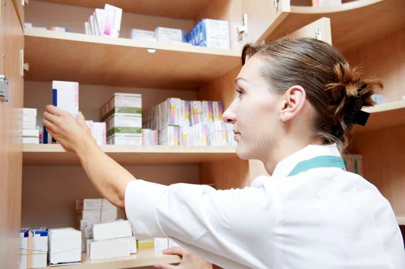 Drogas de rotulagem da mulher do químico da farmácia fotografia de stock royalty free