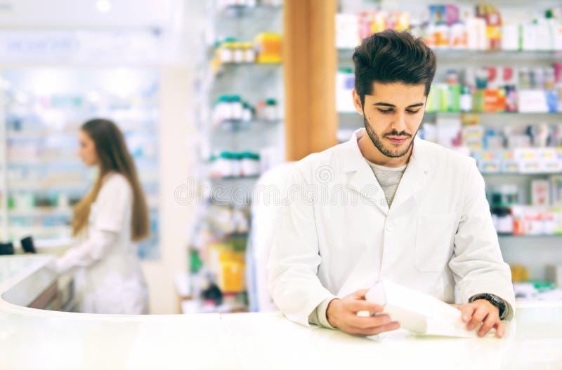 Drogas del embalaje del farmacéutico en la farmacia imagen de archivo