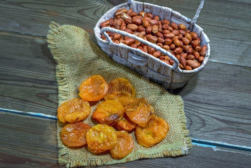 Droge abrikozen en pinda's in een rieten mand op een houten lijst royalty-vrije stock foto's