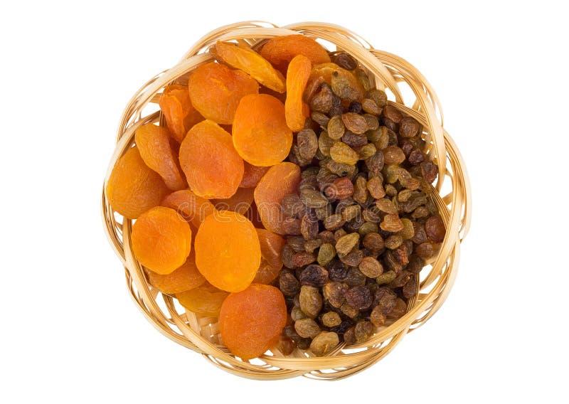 Droge abrikozen en rozijnen in rieten die mand op wit wordt geïsoleerd stock afbeeldingen