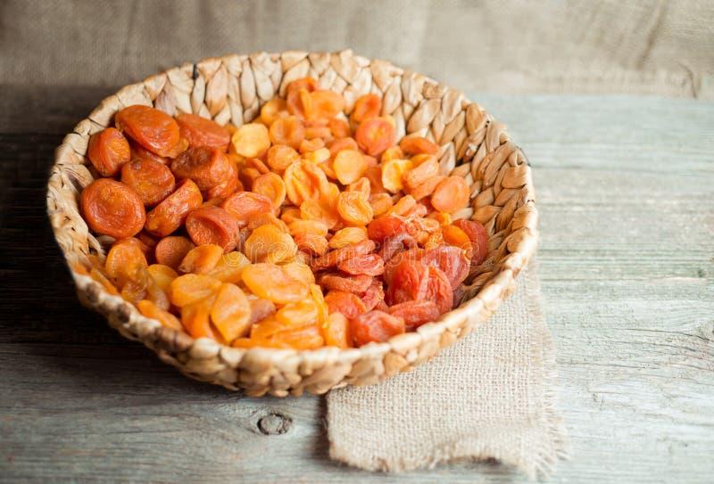 Droge abrikozen in rieten mand op een houten achtergrond, hoogste mening stock foto