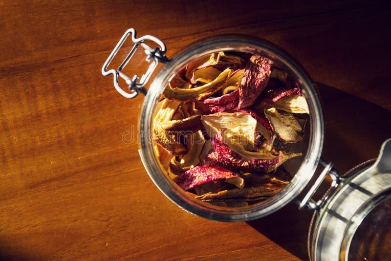 Droge appelen en peren in open glaskruik die op houten lijst, organisch gezond fruitvoedsel liggen, royalty-vrije stock foto