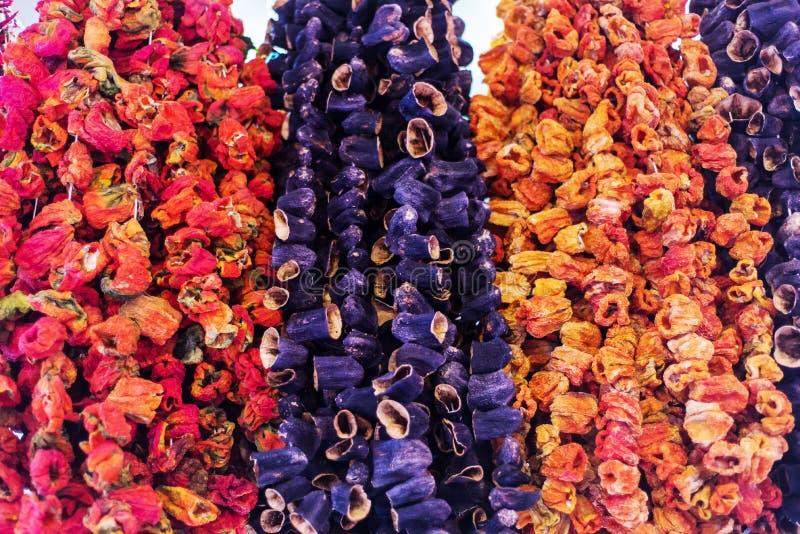 Droge aubergines en groene paprika's die voor een winkel hangen stock afbeelding