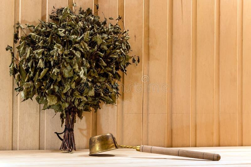 Droge badbezem en lepel in een houten sauna stock afbeeldingen