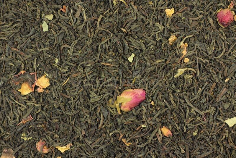 Droge bladeren van zwarte thee met roze bloemblaadjes stock fotografie