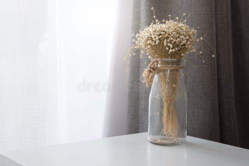 Droge bloem in de transparante fles van de glasvaas bij woonkamer Decoratie en binnenlands concept royalty-vrije stock afbeeldingen