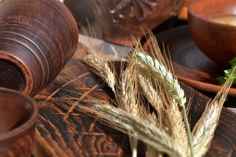 Droge broodaren met ceramische kommen en mok op een bruine houten lijst De herfstoogst van brood stock foto