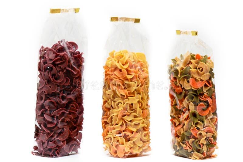 Droge deegwaren in zak vooraanzicht Kleurrijke plantaardige deegwaren op witte achtergrond stock foto