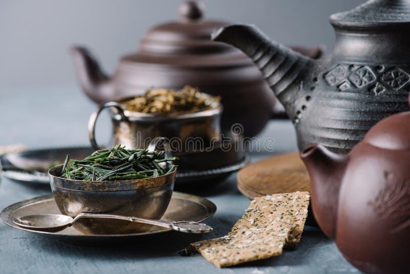 Droge groene thee in kom, knapperige broodplakken en kleitheepotten royalty-vrije stock afbeelding