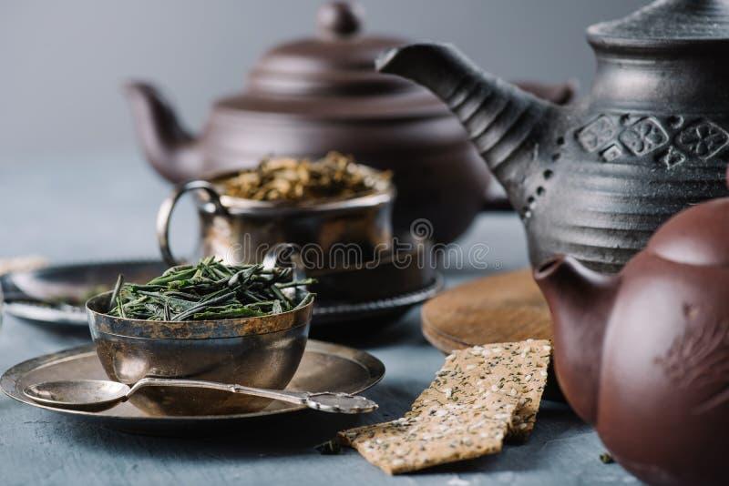 Droge groene thee in kom, knapperige broodplakken en kleitheepotten stock foto's