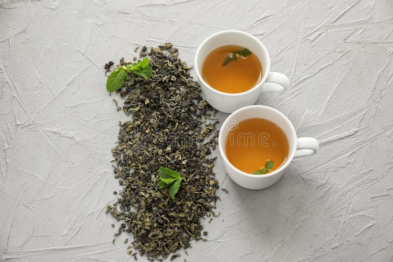 Droge groene theebladen en koppen van aromatische drank op lichte achtergrond royalty-vrije stock foto's