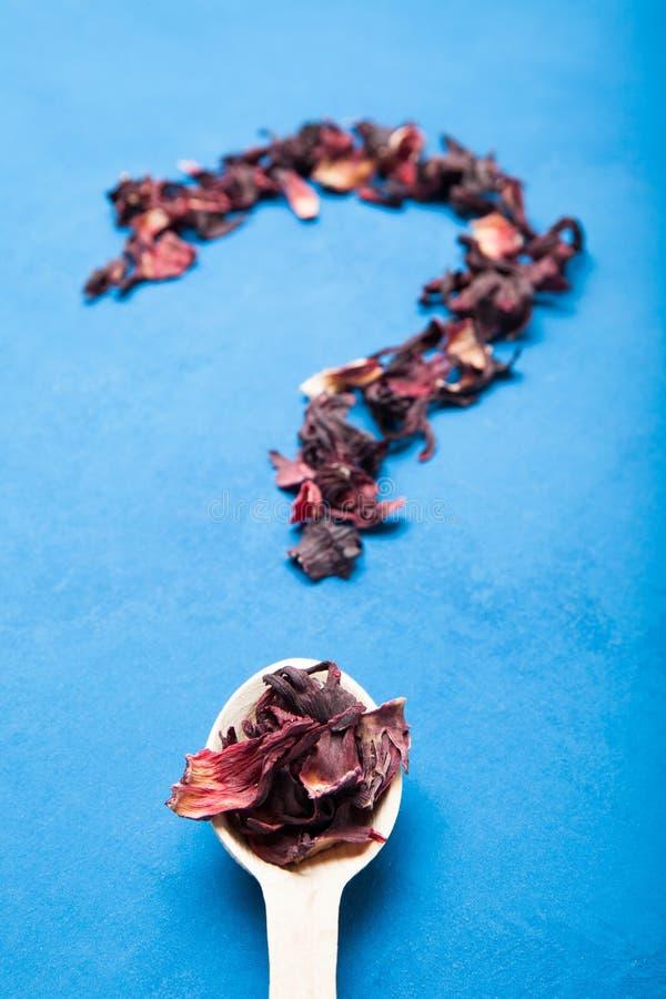 Droge hibiscus in een lepel in de vorm van een vraagteken Achtergrond voor een uitnodigingskaart of een gelukwens royalty-vrije stock fotografie