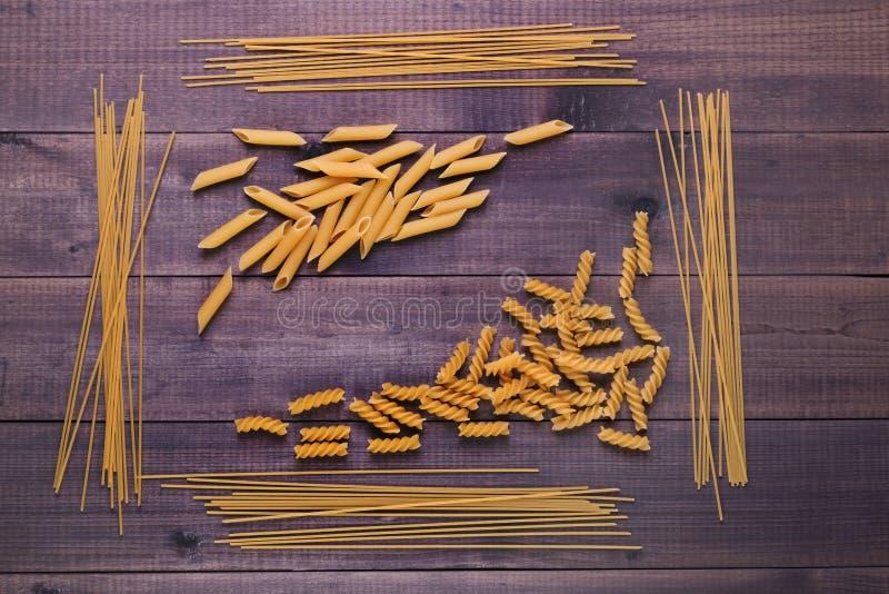 Droge Italiaanse deegwaren - fusilli, spaghetti en penne Verscheidenheid van types en vormen van ongekookte Italiaanse macaroni stock afbeelding