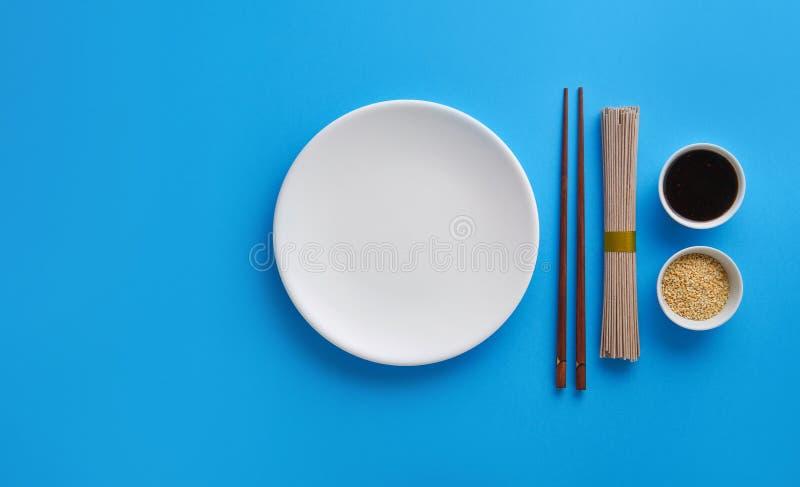 Droge noedelssoba met sojasaus, sesam en eetstokjes op een blauwe achtergrond Vlak leg met hoogste mening stock fotografie