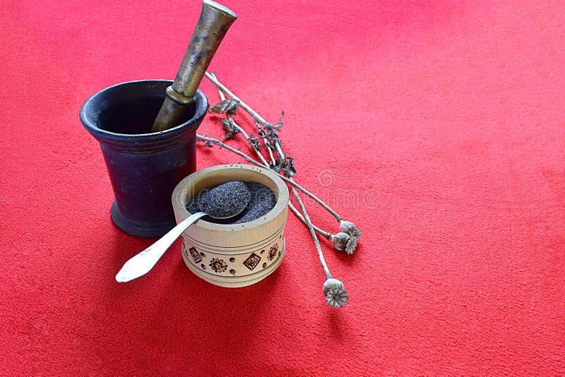 Droge papavercapsules, zaden in een kop en een mortier met stamper royalty-vrije stock afbeelding