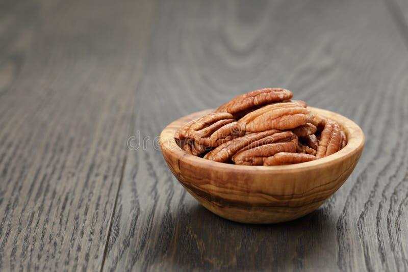 Droge pecannootnoten in olijfkom op houten lijst stock afbeeldingen